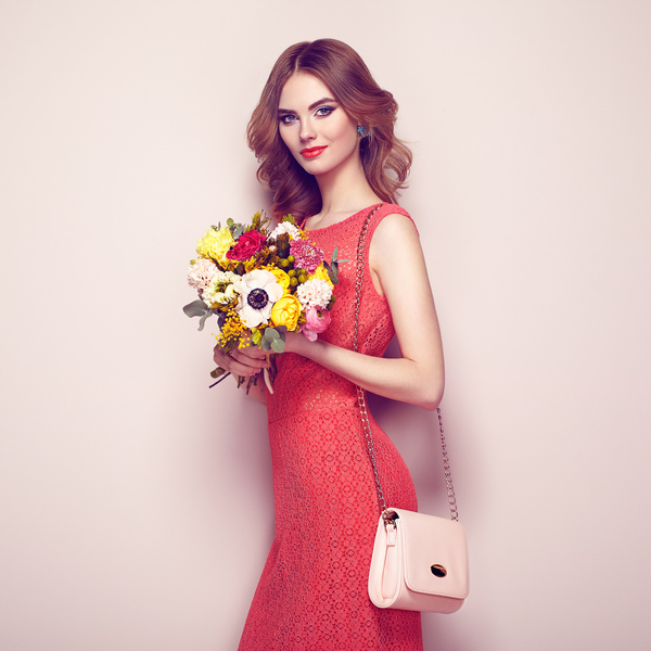 Woman Wearing Red Dress Holding Flowers Pose Stock Photo