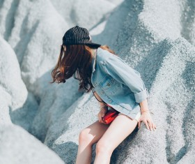 Young attractive woman on white stones cliff Stock Photo