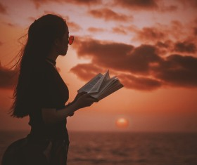 Young girl posing with book on sea sunset Stock Photo