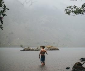 Young man playful on lake in rain Stock Photo
