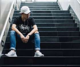 Young people sitting alone on the stairs Stock Photo