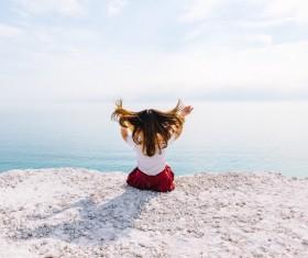 Young woman posing on calm sea scene Stock Photo