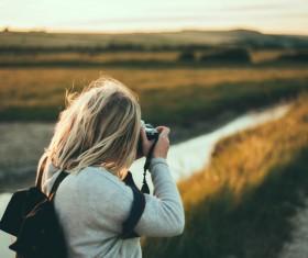 blonde girl enjoying rural scene with camera Stock Photo
