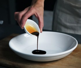 hand pouring sauce into dish Stock Photo