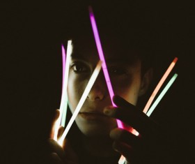 man playful with bright sticks in darkness Stock Photo
