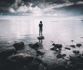 woman standing on rocky beach Stock Photo