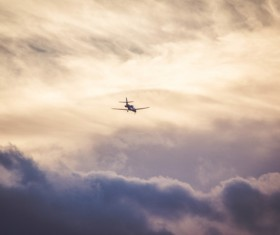 Airplane flying on cloudy sky Stock Photo