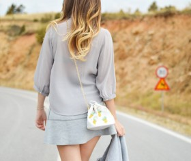 Beautiful young woman walking on road Stock Photo