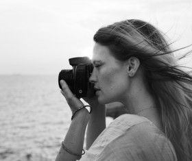 Black white picture of young woman enjoying photographing Stock Photo