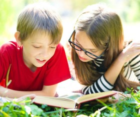 Children reading books on the grass Stock Photo