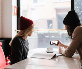 Couple sitting in cafe watching smartphone taking photo Stock Photo 01