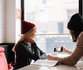 Couple sitting in cafe watching smartphone taking photo Stock Photo 03