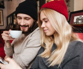 Couple sitting in cafe watching smartphone taking photo Stock Photo 05