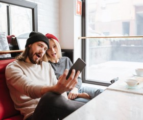 Couple using smartphone selfie in cafe Stock Photo 01