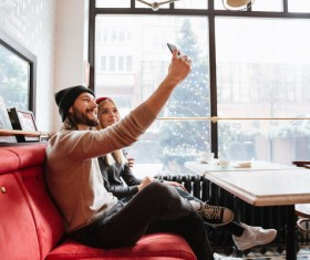 Couple using smartphone selfie in cafe Stock Photo 02