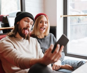 Couple using smartphone selfie in cafe Stock Photo 06