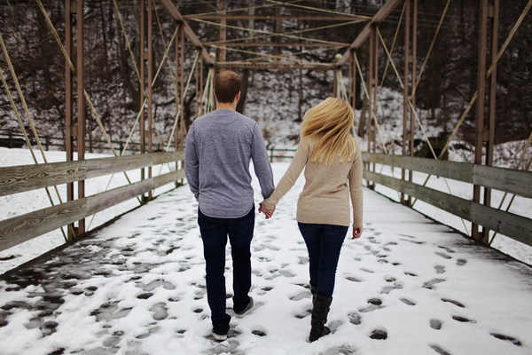 Couple walking hand in hand on the snow Stock Photo