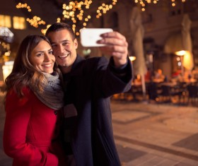 Couples using smartphone selfie on street Stock Photo