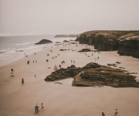 Crowded people gathering on rocky seaside Stock Photo