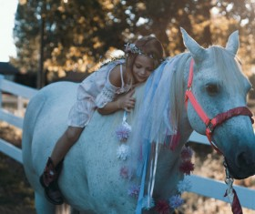 Cute young girl posing on horse back Stock Photo