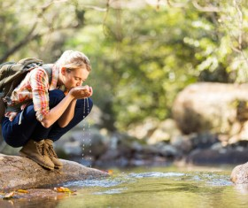 Female tourist drinking spring water Stock Photo