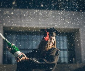 Girl excited with cheering champagne in graduation ceremony Stock Photo