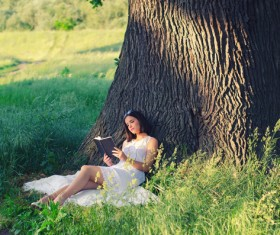 Girl leaning on a tree reading a book Stock Photo