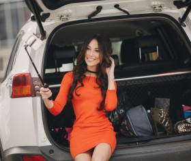 Girl sitting in the car trunk selfie Stock Photo