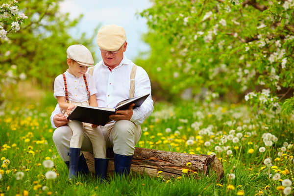 Grandfather and grandson reading book together outdoors Stock Photo