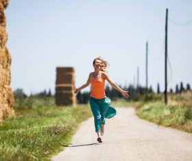 Happy girl running on the road Stock Photo