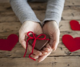 Heart shaped chocolate candy in woman hand Stock Photo