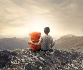 Little boy and toy sitting on the hill Stock Photo