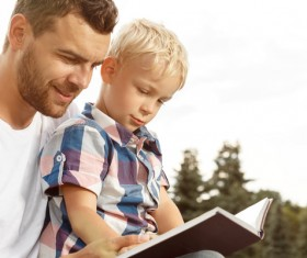 Little boy reading book with dad Stock Photo