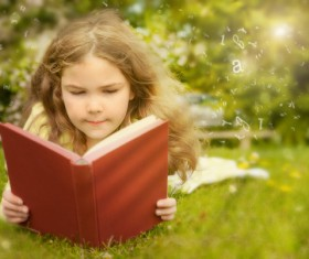 Little girl lying on the grass reading Stock Photo 01