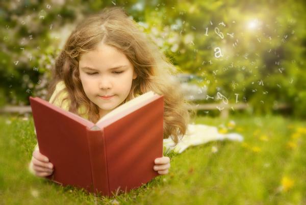 Little girl lying on the grass reading Stock Photo 01