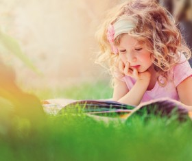Little girl lying on the grass reading Stock Photo 02