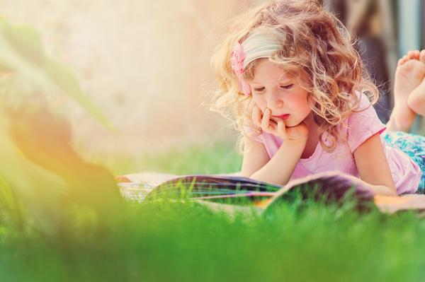 Little girl lying on the grass reading Stock Photo 02
