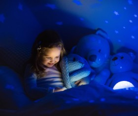 Little girl reading a book at night Stock Photo