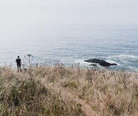Lonely man watching seascape from meadow Stock Photo