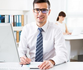 Male salesman sitting in front of computer Stock Photo