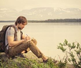 Man sitting by the lake writing Stock Photo
