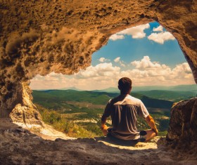 Man sitting in cave mouth meditation Stock Photo