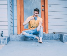 Man sitting in front of the door and drinking beverage Stock Photo