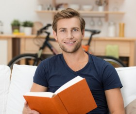 Man sitting on sofa reading a book Stock Photo