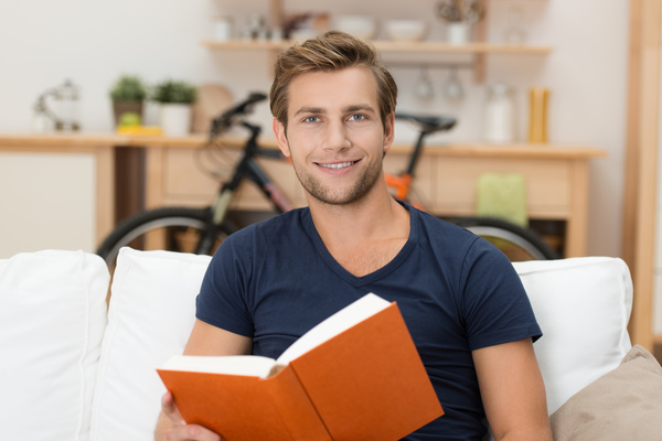 Man sitting on sofa reading a book Stock Photo