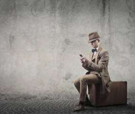 Man sitting on suitcase playing cell phone Stock Photo