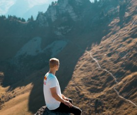 Man sitting on the rock on the mountain and looking at the distant landscape Stock Photo