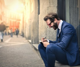 Man sitting on the street recording information smiling Stock Photo