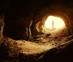 Man standing in a cave mouth Stock Photo