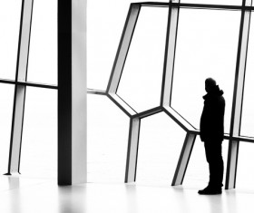 Man standing in front of geometric window Stock Photo